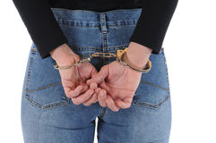 Handcuffed. Young woman with handcuffs in front of a white background stock photography