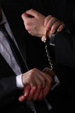 Handcuffed business man. Business man being handcuffed by a police detective, only the hands are visible Stock Photography