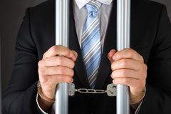 Handcuffed businessman holding bars. Close-up Of Handcuffed Businessman In Jail Holding Metal Bars Royalty Free Stock Image