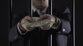 Handcuffed businessman holding dollar banknotes, tax evasion, money laundering stock footage