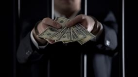 Handcuffed businessman holding dollar banknotes, tax evasion, money laundering stock photography
