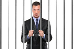 A handcuffed businessman in jail holding bars Royalty Free Stock Image