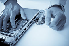 Handcuffed businessman on laptop Royalty Free Stock Image