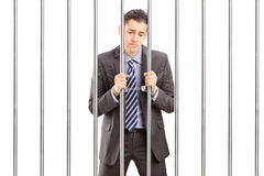 Handcuffed businessman in suit posing in jail and holding bars Stock Photography