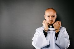Handcuffed Catholic priest. Church harassment and crime concept stock images