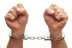 Handcuffed. Closeup of a person handcuffed on a white background Stock Images