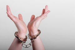 Handcuffed female. Handcuffed hands on a gray background stock photography