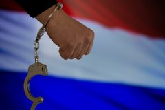 Handcuffed hand in front of the country flag. crime concept. Handcuffed hand in front of the country flag. crime and criminal concept stock photos