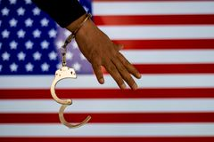 Handcuffed hand in front of the country flag. crime concept. Handcuffed hand in front of the country flag. crime and criminal concept stock image