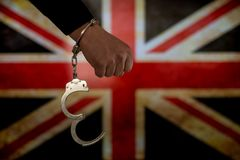 Handcuffed hand in front of the country flag. crime concept. Handcuffed hand in front of the country flag. crime and criminal concept stock images