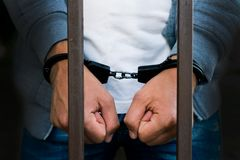 Handcuffed hands of a businessman behind the bars of a prison. C royalty free stock photo