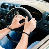 Handcuffed hands of an offender sitting behind the wheel of a ca. R. Concept of arrest the driver, violation of rules and drinking alcohol while driving the car stock photography