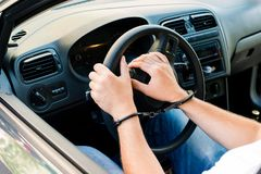 Handcuffed hands of an offender sitting behind the wheel of a ca. R. Concept of arrest the driver, violation of rules and drinking alcohol while driving the car stock photos