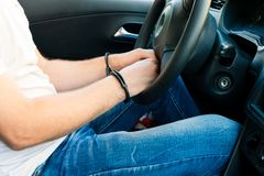 Handcuffed hands of an offender sitting behind the wheel of a ca. R. Concept of arrest the driver, violation of rules and drinking alcohol while driving the car stock images