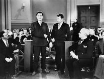 Handcuffed injured man in crowded courtroom. (All persons depicted are no longer living and no estate exists. Supplier grants that there will be no model stock image