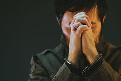 Handcuffed male prisoner in military uniform is praying Royalty Free Stock Images