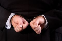 Handcuffed Man. Close up of man wearing suit handcuffed behind his back Stock Image