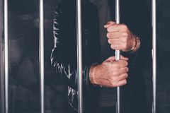 Handcuffed man behind prison bars. Arrested criminal male person imprisoned Royalty Free Stock Photography