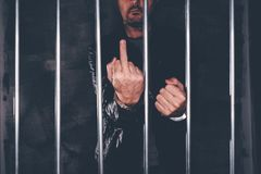 Handcuffed man behind prison bars giving middle finger. As rude hand gesture. Arrested criminal male person imprisoned royalty free stock photo