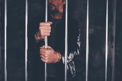 Handcuffed man behind prison bars. Arrested criminal male person imprisoned Stock Images