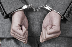 Handcuffed man. A man wearing a suit, with handcuffs in his wrists Royalty Free Stock Photos