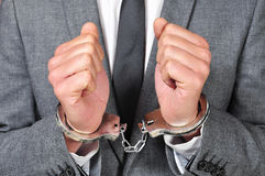 Handcuffed man. A man wearing a suit, with handcuffs in his wrists Royalty Free Stock Photo