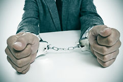 Handcuffed man. A man wearing a suit sitting in a desk, with handcuffs in his wrists Royalty Free Stock Photos