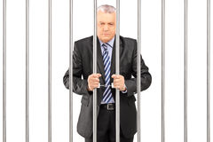 A handcuffed manager in suit posing in jail and holding bars. On white background Stock Photos