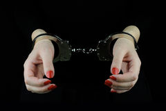 Handcuffed woman hands. On black background Stock Photography
