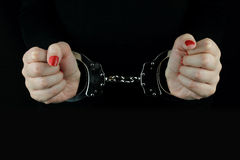 Handcuffed woman hands. On black background Royalty Free Stock Images