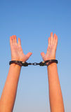 Handcuffed woman hands. Against blue sky Stock Image