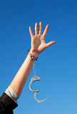 Handcuffed woman's hand. Against blue sky Royalty Free Stock Photo