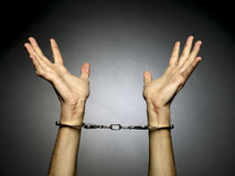 Handcuffs. A man hands  with handcuffs isolated on black background Royalty Free Stock Photos