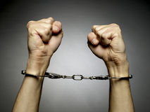 Handcuffs. A man hands  with handcuffs isolated on black background Royalty Free Stock Image