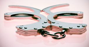 Handcuffs. Isolated handcuffs on a pink backdrop stock photography
