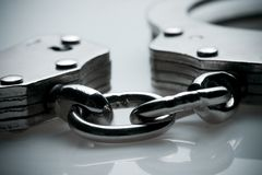 Handcuffs. Macro shot of a pair of handcuffs with focus on the chain royalty free stock photography