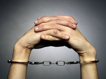 Handcuffs. A man hands  with handcuffs isolated on black background Royalty Free Stock Photography