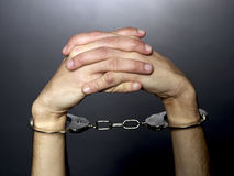 Handcuffs. A man hands  with handcuffs  on black background Stock Photos