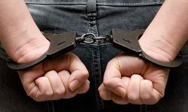 Handcuffs. Hands bounded with handcuffs symbol for crime Royalty Free Stock Photos