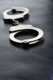 Handcuffs. On a black leather background Stock Photos