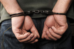 Handcuffs. Hands of criminals being handcuffed Royalty Free Stock Photos