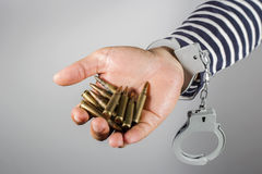 Handcuffs and ammunition. Concept of criminal acts and the ammunition in his possession Royalty Free Stock Photos