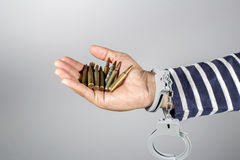 Handcuffs and ammunition.Concept of criminal acts. Handcuffs and ammunition.Concept of criminal acts and the ammunition in his possession Royalty Free Stock Photo