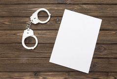 Handcuffs. A blank piece of paper against the background. Of a wooden table. arrest. confession. denunciation. a crime Royalty Free Stock Photography