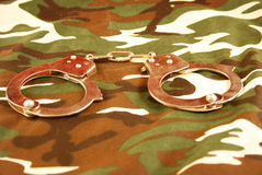 Handcuffs on camouflage Stock Photography