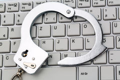 Handcuffs on computer keyboard Royalty Free Stock Photography