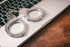 Handcuffs on a computer on a wooden background. stock image
