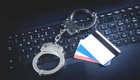 Handcuffs with credit cards on computer keyboard. Concept of Cyber crime and Online fraud royalty free stock photos