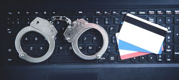 Handcuffs with credit cards on computer keyboard. Concept of Cyber crime and Online fraud stock images