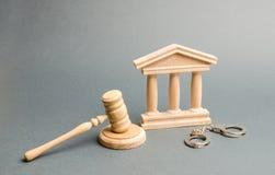 Handcuffs, de hamer van de rechter en gerechtsgebouw Bescherming van de gedaagde in het strafzaak Beschermingsstrategie oordeel royalty-vrije stock afbeeldingen